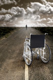Recovery. Man abandons the wheelchair and recommences to walk Royalty Free Stock Image