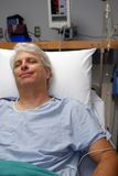 Recovery. Gray haired man in hospital bed smiling after surgery Stock Images