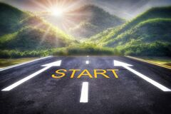 Start word written on road and white arrow with sunrise