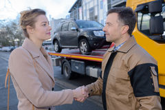 Recovery driver shaking hands with owner car Royalty Free Stock Photography