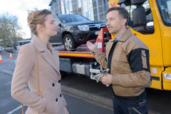 Recovery man with customer`s car on lorry Stock Image