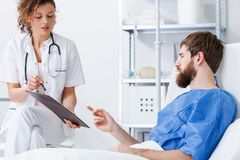 Recovery nurse talking with patient. Recovery nurse talking with young trauma patient in hospital royalty free stock photo