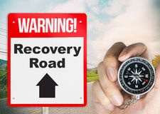 Recovery Road concept sign with holding compass Stock Image