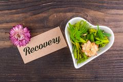 Recovery word on card. With dried flower and heart shape bowl on wood Royalty Free Stock Photos