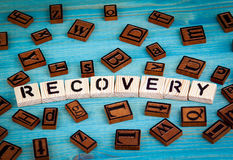 Recovery word written on wood block. Wooden alphabet on a blue background Royalty Free Stock Photo