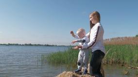 Recreação exterior da família, mulher feliz com alimento do lance do bebê na água para peixes no lago durante feriados filme
