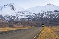 Recreatief voertuig op Ijslandse weg met sneeuw afgedekte berg stock foto's