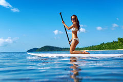 Recreatieve Watersporten Vrouw die op Brandingsraad paddelen De zomer Stock Fotografie
