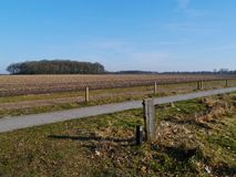 Recreation and agriculture landscape. A paved bike path in perspective along a field lying fallow in Drenthe in the Netherlands Royalty Free Stock Image
