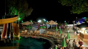 Recreation area with a hotel pool at night. People quickly go to the bar and talk to each other. TimeLapse stock video