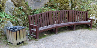 Recreation area with a wooden bench and a basket for garbage. In the mountain public park Stock Images
