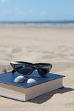 Recreation on the beach. A book and sunglasses lying in the sand, symbolizing recreation Royalty Free Stock Images