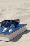 Recreation on the beach. A book and sunglasses lying in the sand, symbolizing recreation Royalty Free Stock Image