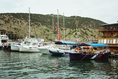 Recreation on a boat at the shore of a beautiful mountain. Yachts and boats in the beautiful Bay of Balaklava. Picturesque fishing stock photography
