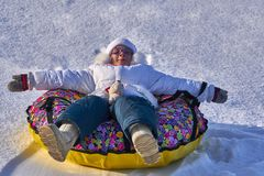 Recreation. A child  girl is resting after a toboggan run. She lies on the sledge tubing. Sunny winter frosty day Stock Photography