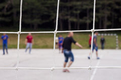 Recreation concept. Close up of net with football players in the playground Stock Images
