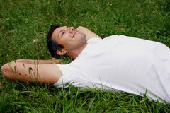 Recreation man. Man lying in green with flowers Royalty Free Stock Images