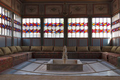 Recreation room in the Khan's Palace Bakhchisaray. Sofas, a fountain and stained glass Windows of the relaxation room at the Palace of Bakhchisarai Royalty Free Stock Photography