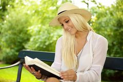 Recreation on a sunny day. Bright portrait of a cute woman reading a book on a sunny day Royalty Free Stock Images