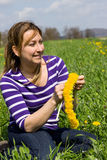 Recreation time. Woman weaves a wreath of flowers on a green meadow Stock Photos