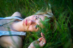 Recreation. Young girl lying in grass resting Royalty Free Stock Photography