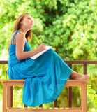 Young woman writing to notebook. Outdoor portrait Royalty Free Stock Photos