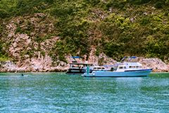 Recreational boats anchoring near small islands. A group of unrecognizable people having fun activities on holidays vacation. Recreational boats anchoring near stock images
