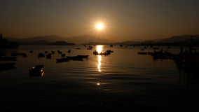 Recreational and fishing boats at sunset. The shadow of some recreational and fishing boats are at sunset stock image