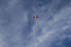 Recreational, Kite of rainbow colors on a blue sky with light wh Royalty Free Stock Photo