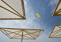 Recreational parasailing. A person parasailing over a beach full of parasol Royalty Free Stock Photo