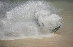 Kitesurfer in action on tropical sea. Recreational sport kitesurfer surfing over lagoon in tropcial sea with wake splash Royalty Free Stock Photos