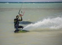 Kitesurfer in action on tropical sea. Recreational sport kitesurfer surfing over lagoon in tropcial sea with wake splash Royalty Free Stock Photo