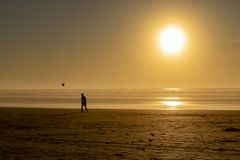 Silhouette of a man on a beach heading a football at sunset stock photos