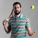 Recreational tennis player holding racket and tossing ball. In mid air Stock Photo