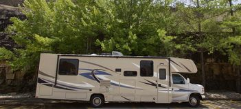 Recreational Vehicle parked in front of mountain. Royalty Free Stock Photography