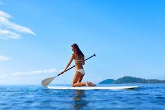 Recreational Water Sports. Woman Paddling On Surf Board. Summer. Recreational Water Sports. Healthy Happy Fit Woman With Sexy Body Paddling, Kneeling On Stand Up Stock Image