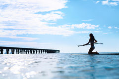 Recreational Water Sports. Woman Silhouette On Surfboard In Ocean. Wellness. Recreational Water Sports. Silhouette Of Free Fit Woman Paddling, Kneeling On Stand royalty free stock image