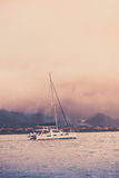 Recreational Yacht in fog at the coast of Seychelles Royalty Free Stock Photography