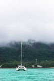 Recreational Yacht in fog at the coast of Seychelles Royalty Free Stock Photo