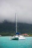 Recreational Yacht in fog at the coast of Seychelles Stock Photos