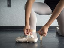 Recreational young female ballet dancer ballerina, in the studio putting on her pointe shoes, tying up. Her ribbons for dance class royalty free stock photos