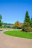Recreational zone with tiled pathway in front. Park zone. Recreational area with green lawn and trees Stock Image