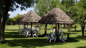 Recreative park benches and palm leaves tents. Some white plastic benches awaiting for the visitors in a vacations park in some place in mexico stock photos