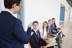 Recruiter die baankandidaten richten die op gesprekken wachten stock afbeeldingen