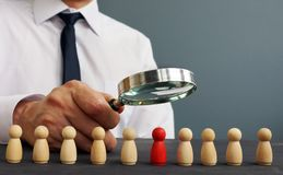 Recruiter looking through magnifying glass on candidates. Hiring and recruiting. Concept stock images