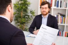 Recruiter reading curriculum of a candidate for a job Stock Image