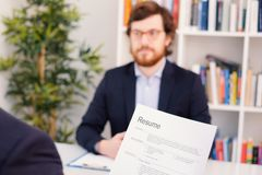 Recruiter reading curriculum during job interview royalty free stock photo