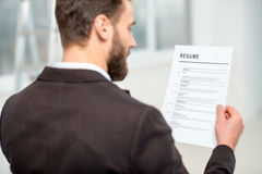 Recruiter with resume paper. Elegant recruiter reading resume for job hiring in the office stock photos