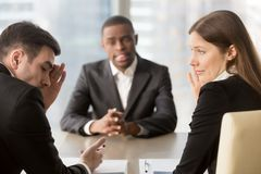 Recruiters covertly deciding to refuse applicant. Skeptical female and male caucasian employers covering face with hand and whispering while discussing african Stock Photo
