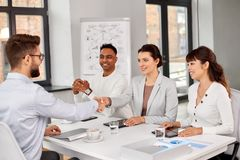 Recruiters having interview with employee. Job, hiring and employment concept - international team of recruiters having interview with male employee and shaking royalty free stock image